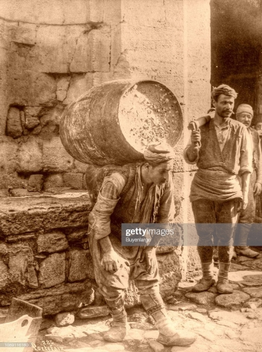 Porter carries a huge barrel on his back, Istanbul, Turkey, 1920. (Photo by Portafaiz/Buyenlarge/Getty Images)